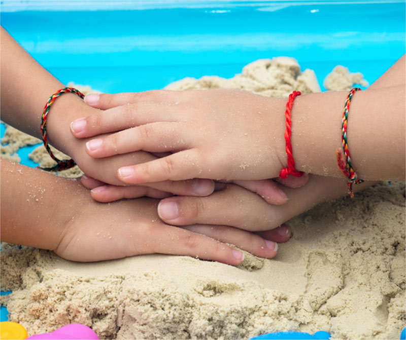 Friends' hands in the sand