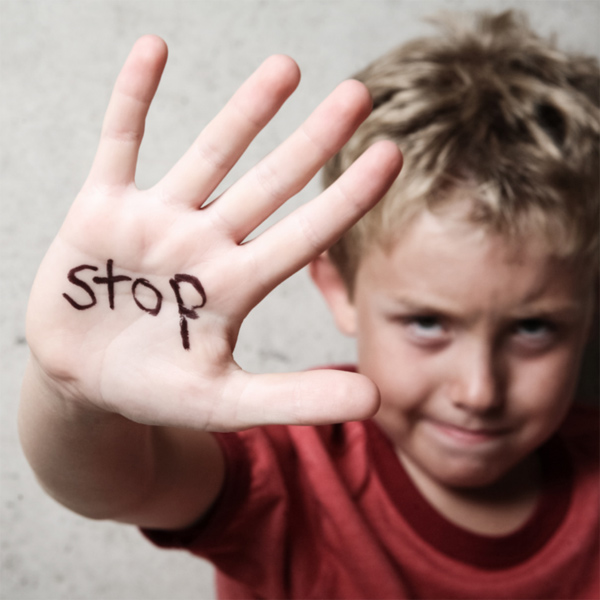 Boy with the word 'stop' written on his hand