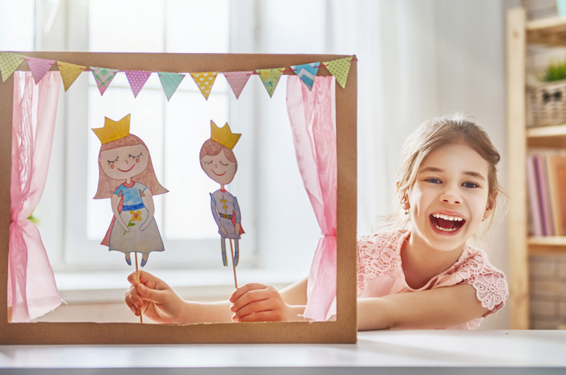 Girl playing with a puppet theatre